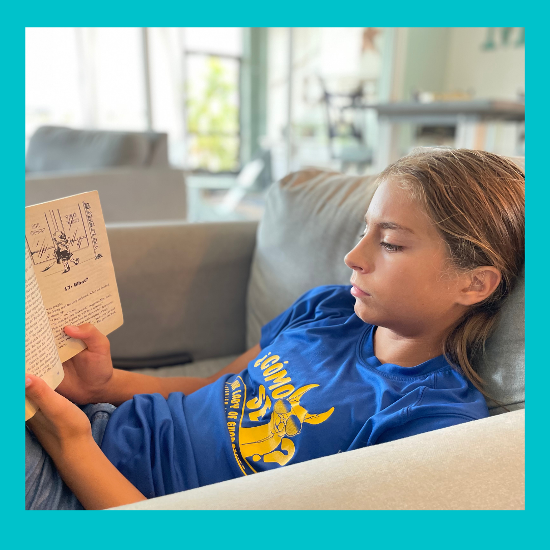 A girl reading a book for the Book Reviews for kids on Wayside School is Falling Down.