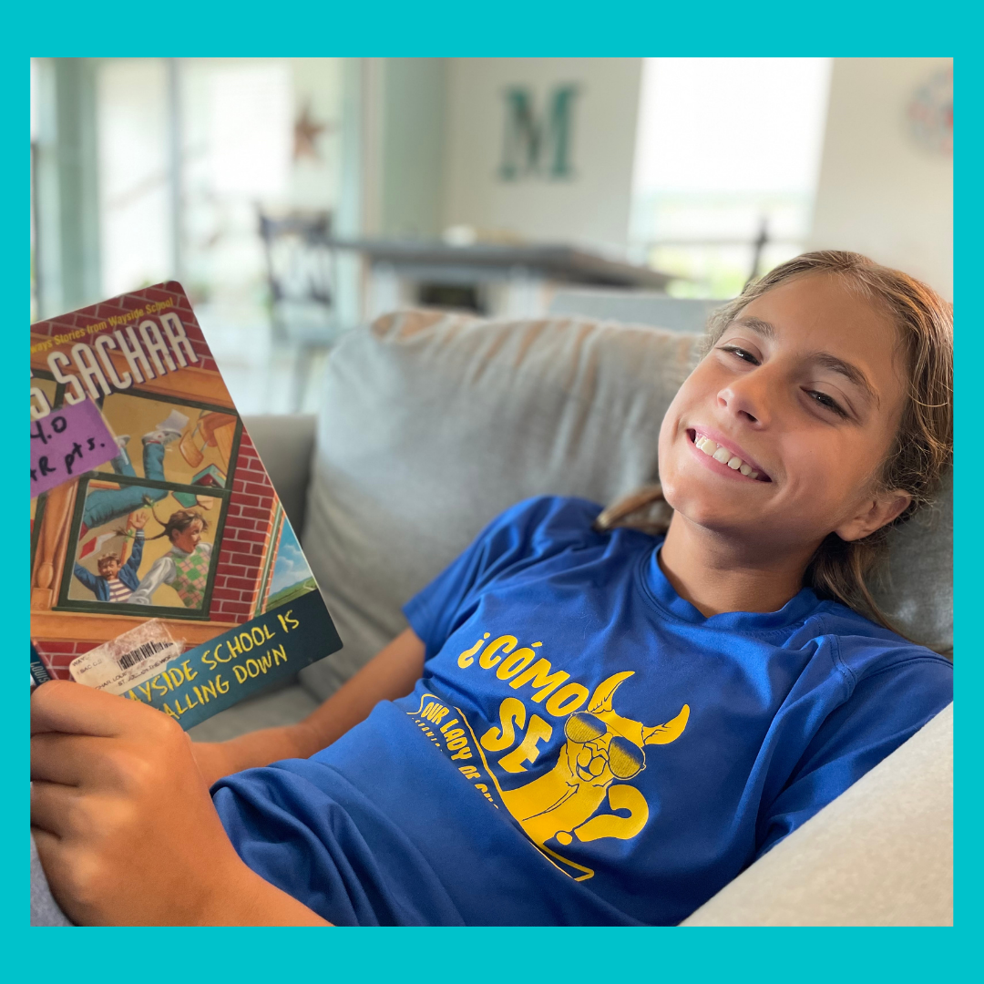 picture of a girl smiling while reading Wayside School is Falling Down.