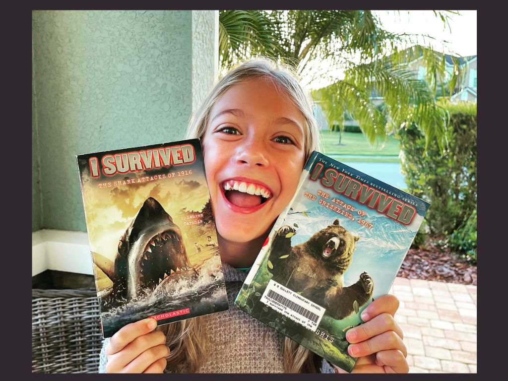 A young girl from K and B Life holding up her 2 favorite I Survived Books for the Book Review.