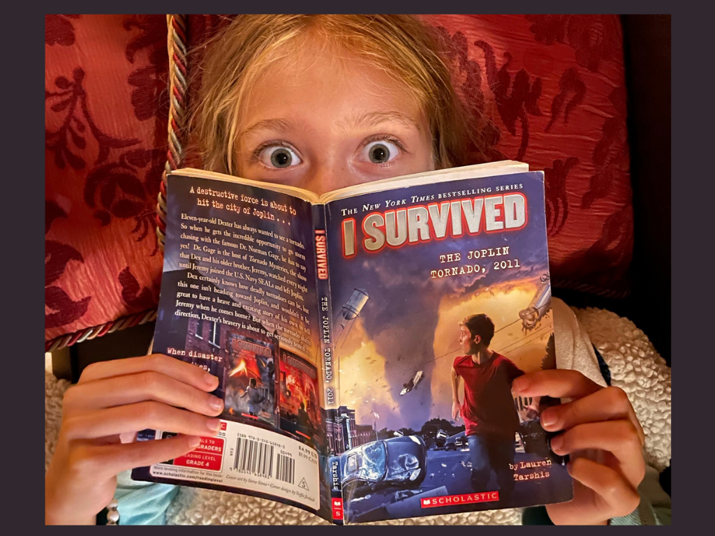 A young girl looking over the book, I Survived the Joplin tornado, with huge, wide eyes.