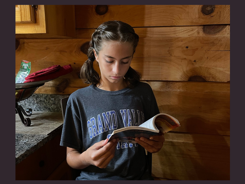 A girl reading a book for the I survived Book review by K and B Life