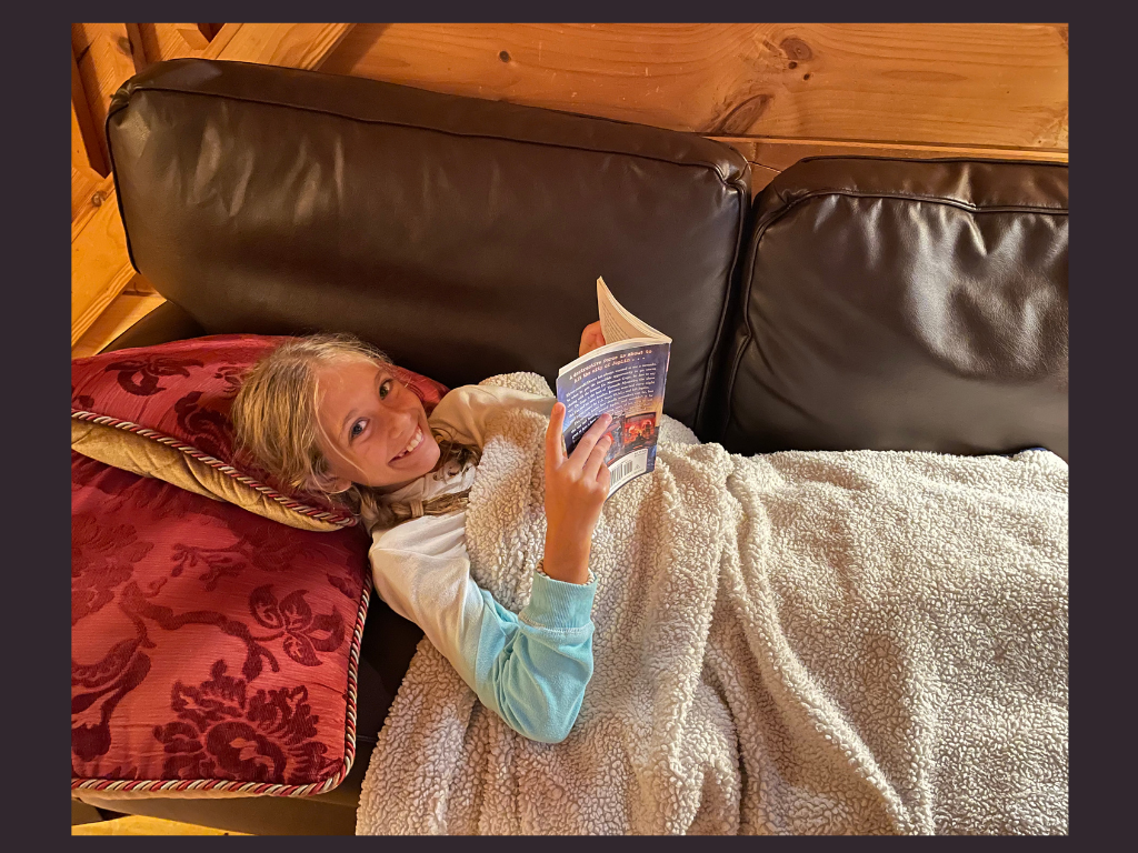 A girl reading on a couch.